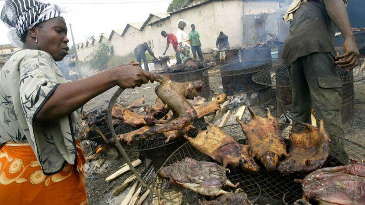 Une femme fumant de la viande de brousse sur un marché en Afrique