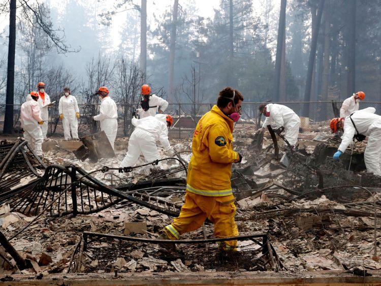 Des pompiers et des membres d'une équipe de recherche et de sauvetage bénévoles s'approchent d'une maison détruite par l'incendie du camp à Paradise, Californie, États-Unis, le 13 novembre 2018. REUTERS / Terray Sylvester