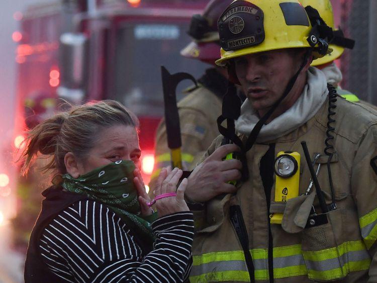 Un résident de la région s'entretient avec des pompiers en poste le long de la route de la côte du Pacifique (autoroute 1) pour combattre l'incendie de Woolsey le 9 novembre 2018 à Malibu, Californie