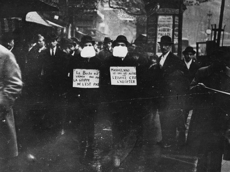 Des hommes portant des masques antigrippaux à Paris pendant l'épidémie de grippe espagnole qui a suivi la Première Guerre mondiale