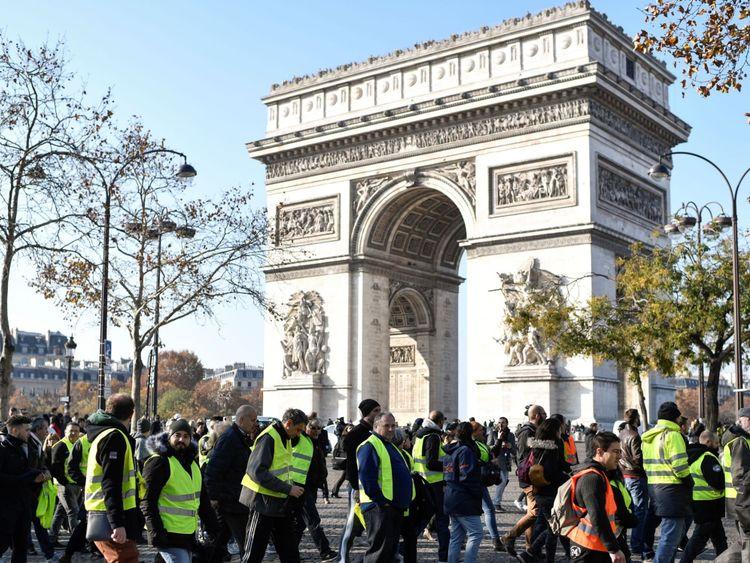 Des manifestants portant des gilets jaunes (Gilets jaunes) défilent devant l'Arc de Triomphe à Paris le 17 novembre 2018 lors d'une manifestation contre la hausse des prix du carburant et de l'huile