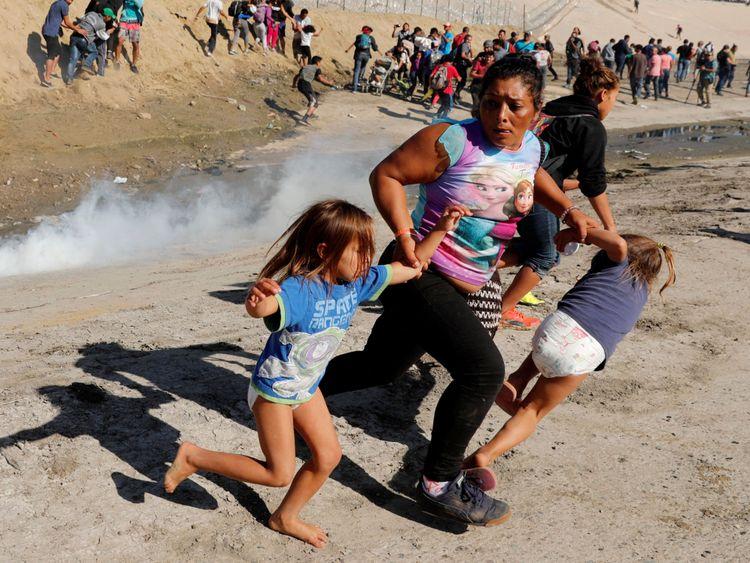 Une famille de migrants du Honduras, échappe aux gaz lacrymogènes émis par une patrouille de frontière américaine près de la barrière entre le Mexique et les États-Unis à Tijuana