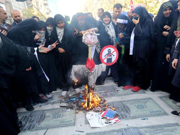 Des manifestants iraniens brûlent l'effigie du président américain placée sur d'énormes copies d'un billet de banque américain de 100 dollars