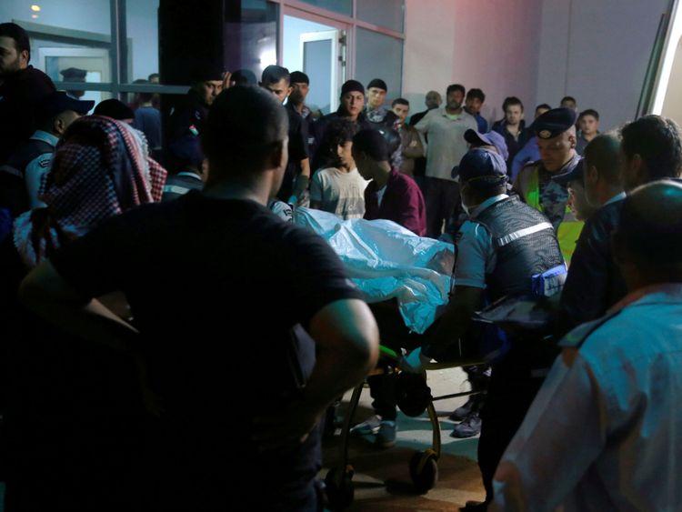 Les résidents et les proches des victimes des inondations se rassemblent devant un hôpital situé près de la mer Morte en Jordanie le 25 octobre 2018