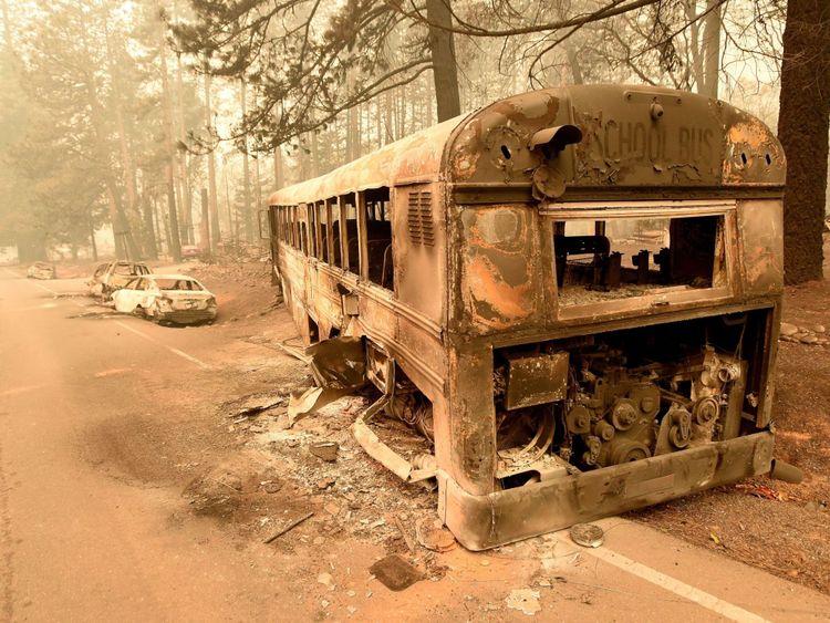 Des voitures incendiées abandonnées et un autobus scolaire assis au bord d'une route à Paradise en Californie
