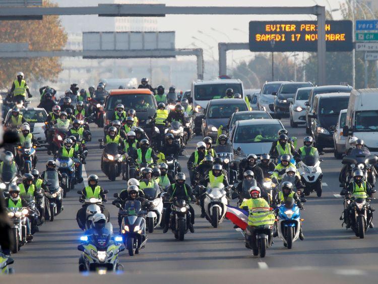 Les motocyclistes portant des gilets jaunes, symbole des conducteurs français & # 39; Manifestation contre la hausse des prix du carburant, avancez le pas d'un escargot en bloquant la rocade à Paris, en France, le 17 novembre 2018