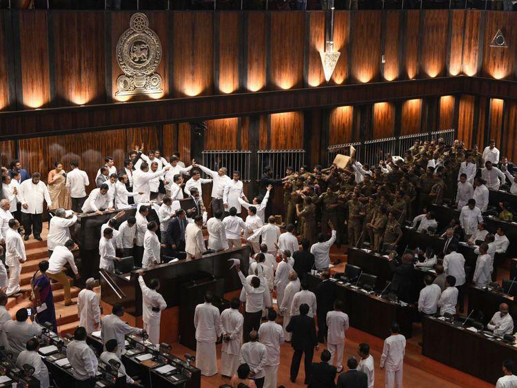 La police sri-lankaise (R) se réunit pour escorter le président du Parlement, Karu Jayasuriya, dans la salle de réunion, alors que des législateurs rivaux (L) occupent le siège du président à Colombo le 16 novembre 2018. - Le président du Parlement de Sri Lanka a demandé la police la protection en tant que violence revint à la législature pour une deuxième journée le 16 novembre, les factions rivales dans la crise constitutionnelle de l'île ne montrant aucun signe de recul. Un groupe de législateurs occupa la présidence du président Karu Jayasuriya pendant 50 minutes.