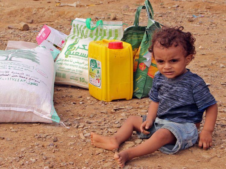 Un enfant déplacé d'Hodeida assis à côté de l'aide alimentaire