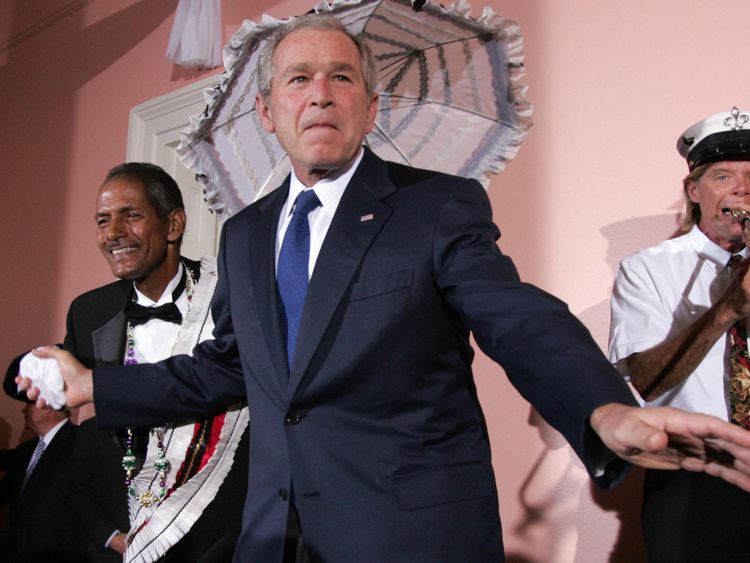 Le président américain George W. Bush (C) danse avec le Burnell Brunious (L), grand maréchal du groupe de brass dixie Euphonious, lors d'une réception de la Chambre de commerce des États-Unis à Gallier Hall à la Nouvelle-Orléans, en Louisiane, le 21 avril 2008. AFP PHOTO / SAUL LOEB (Le crédit photo doit correspondre à SAUL LOEB / AFP / Getty Images)