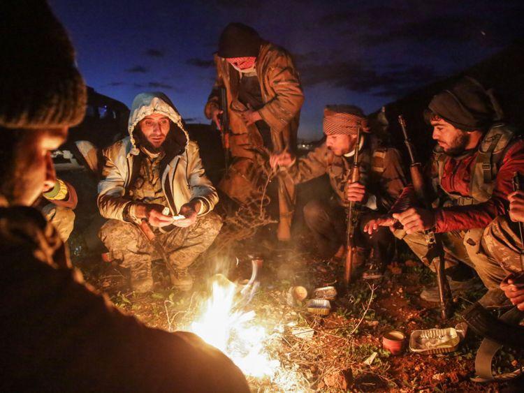 Des combattants syriens soutenus par la Turquie se réchauffent autour d'un feu près de Manbij
