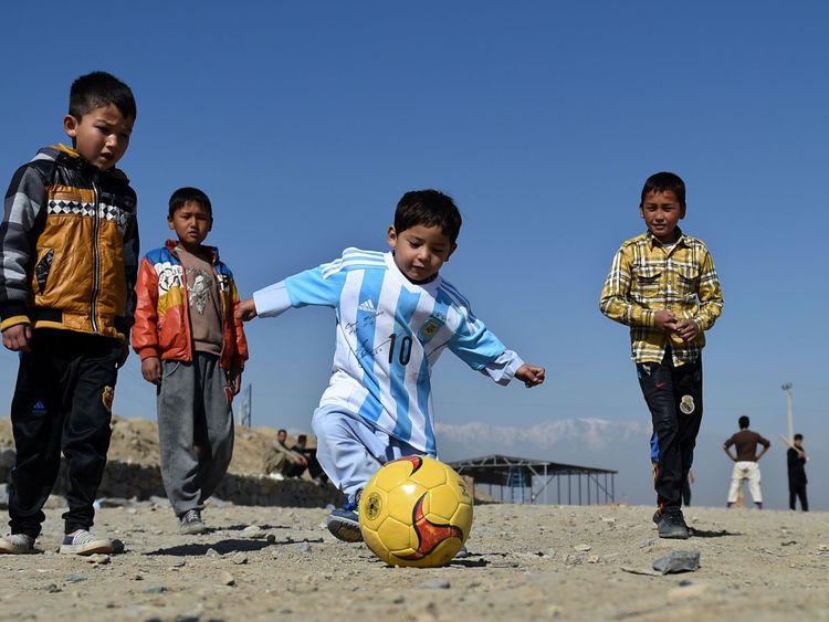 Le jeune joue au football dans sa chemise Messi signée