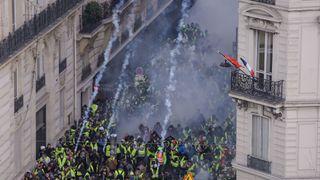& # 39; Gilet jaune & # 39; Des manifestants se heurtent à la police anti-émeute au milieu des gaz lacrymogènes sur les Champs-Élysées à Paris.