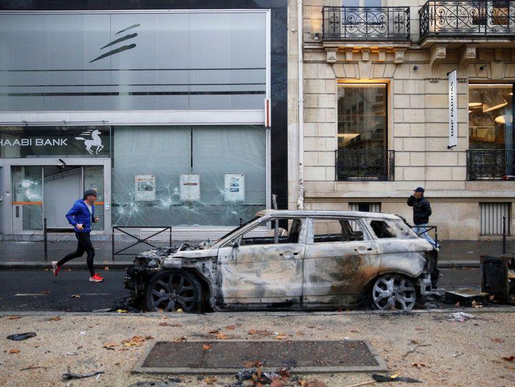 Une voiture et un front de banque vandalisés sont visibles le matin après des affrontements avec des manifestants portant des gilets jaunes, symbole des conducteurs français. Protestation contre la hausse des taxes sur le carburant diesel, à Paris (France), le 2 décembre 2018.