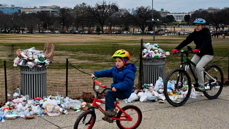 La Maison Blanche apparaît à l'arrière-plan alors que les gens passent à vélo devant les ordures non ramassées dans le National Mall, en raison de la fermeture partielle du gouvernement américain le 2 janvier 2019 à Washington, DC