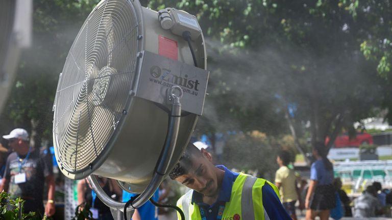 Un homme se rafraîchit devant un fan de brume pour se soulager de la chaleur du 12ème jour du tournoi de tennis de l'Australian Open à Melbourne