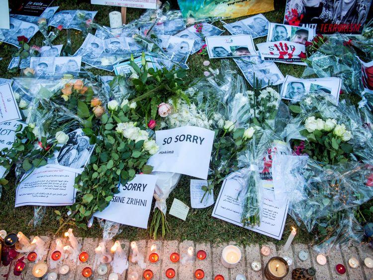 Cette photo montre des textes, des images et des bougies posées pendant que les Marocains rendent hommage à la Danoise Louisa Vesterager Jespersen et à la Norvégienne Maren Ueland, assassinées, à Rabat, devant l'ambassade de Norvège le 22 décembre 2018.