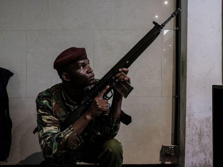 Un officier armé sécurise un bâtiment rattaché au complexe où l'attaque a eu lieu