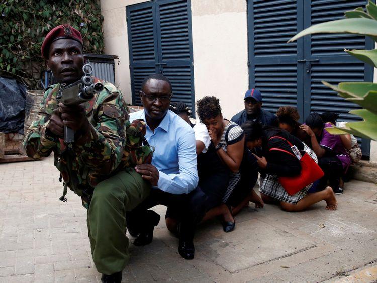 Des personnes sont évacuées du complexe par un membre des forces de sécurité