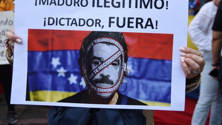 """Un manifestant porte une pancarte """"Maduro, illégitime, dictateur, sors!"""" au Guatemala, devant l'ambassade du Venezuela"""