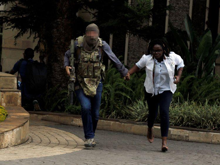 Un agent de sécurité évacue une femme blessée