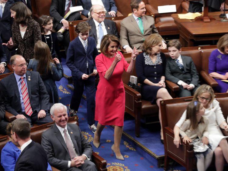 La représentante du Président désignée, Nancy Pelosi (D-CA) donne un double coup de pouce pour entrer dans la salle des séances.