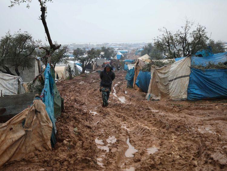 Des Syriens déplacés marchent dans un camp inondé près de Kah, dans la province d'Idlib, au nord-est de la Syrie.