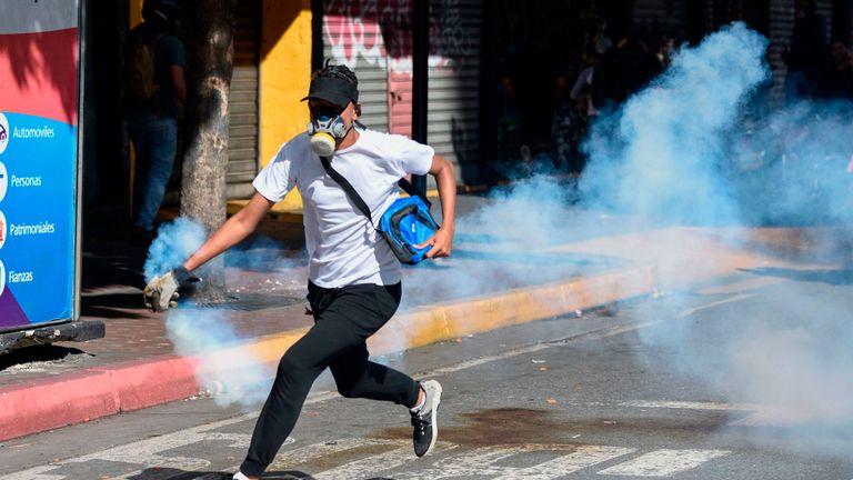 Un manifestant de l'opposition court avec une cartouche de gaz lacrymogène
