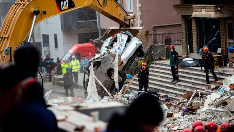 Des secouristes fouillent les décombres d'un immeuble de huit étages après son effondrement