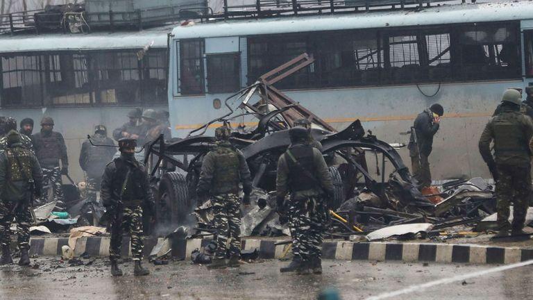 Les forces de sécurité inspectent les restes d'un véhicule détruit lors d'un attentat à la bombe ayant tué au moins 41 soldats