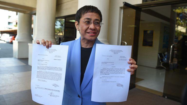 Maria Ressa en 2018 avec son mandat d'arrêt pour une accusation de fraude fiscale
