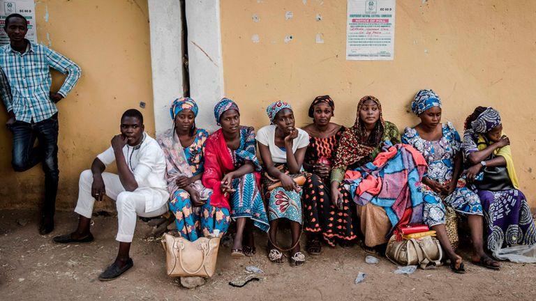 Un groupe de femmes assises à l'entrée d'un bureau de vote à Gombi