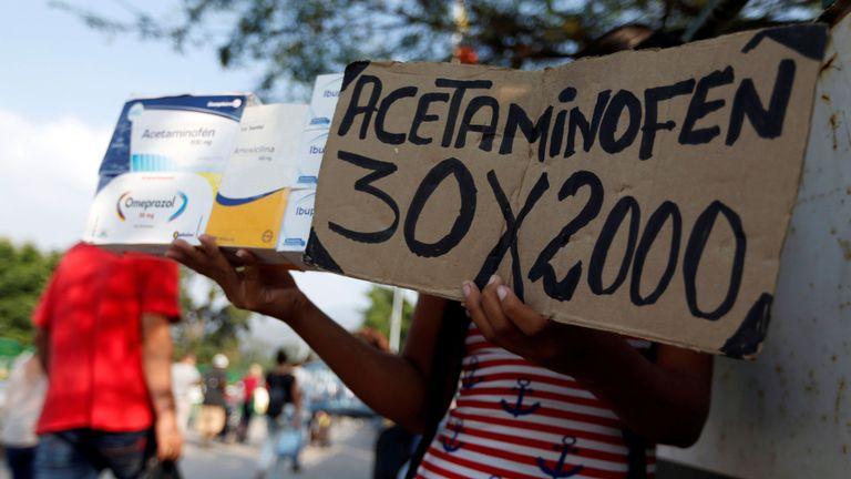 """Une femme tient une pancarte """"Acétaminophène 30 x 2000"""" sur le pont international de Simon Bolivar"""