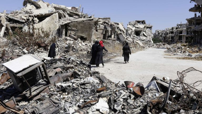 Trois femmes marchent dans des bâtiments détruits à Homs