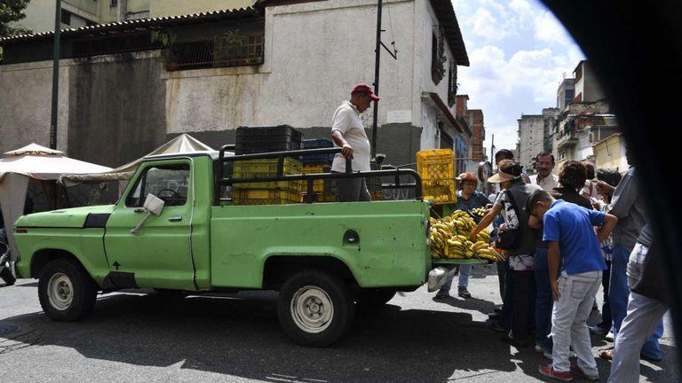 Les gens se rassemblent autour d'un homme vendant des bananes dans son camion dans un marché de rue de Caracas