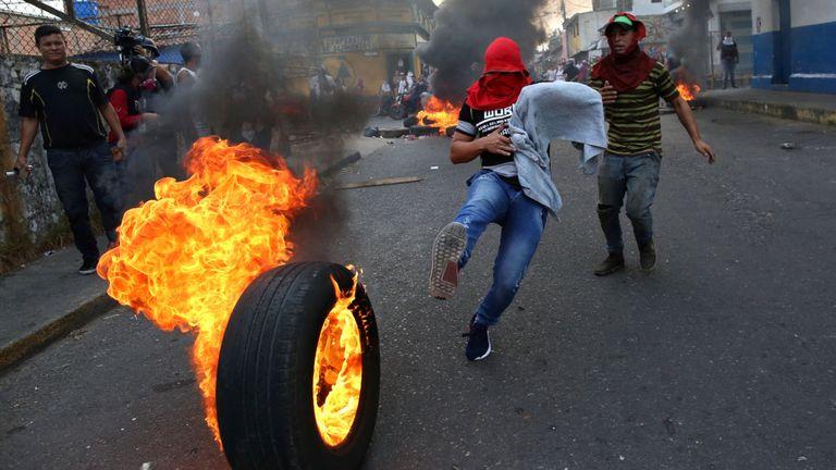 Un manifestant donne un coup de pied dans un pneu brûlant à Urena