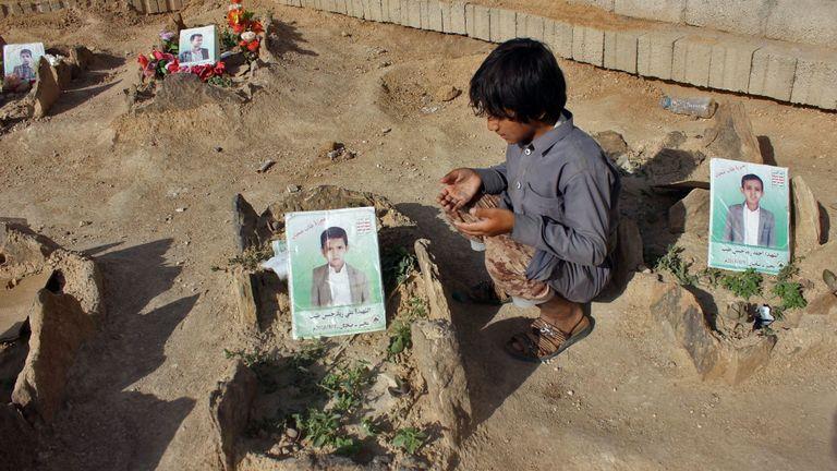 Un enfant yéménite récite une prière sur les tombes de collégiens décédés dans un bus frappé par un raid aérien dirigé par la coalition saoudienne