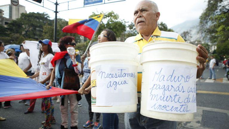 """Les signes de cet homme indiquent: """"Nous avons besoin d'eau"""". et à droite, Maduro, tu paieras pour la mort des innocents."""