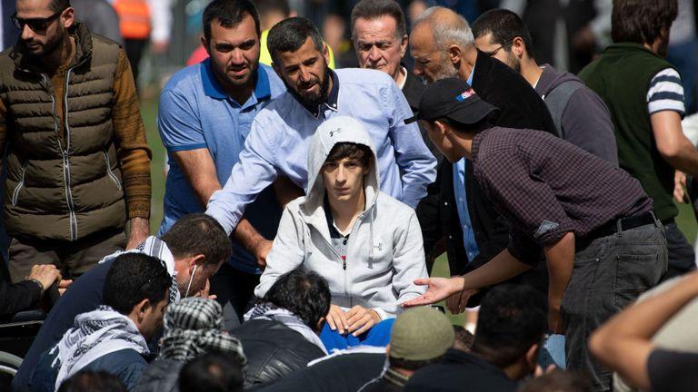 Zaid Mustafa (C, en fauteuil roulant), qui a été blessé dans les attaques arrive pour prier