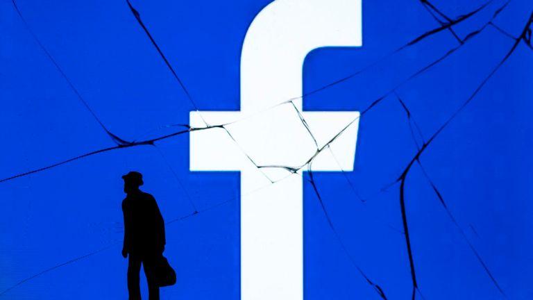 Cette photo prise le 16 mai 2018 montre une figurine se tenant devant le logo du réseau social Facebook sur un écran fissuré d'un smartphone à Paris.