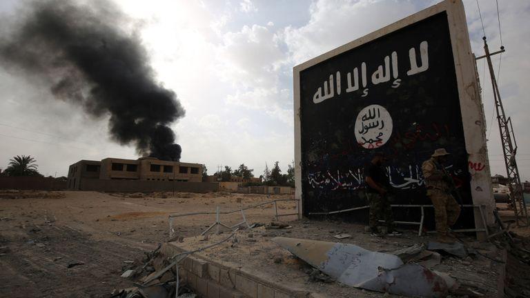 Un combattant irakien se tient près d'un mur portant le drapeau du groupe IS à Al Qaim
