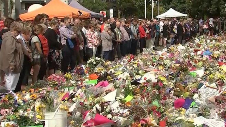 Les personnes en deuil se rassemblent et laissent des fleurs comme un pays se souvient des victimes