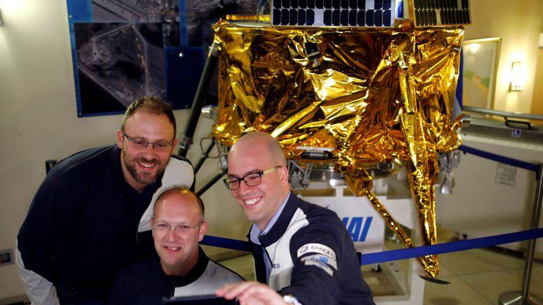 Les gens de SpaceIL et Israel Aerospace Industries (IAI) réalisent un selfie devant un modèle de vaisseau spatial Beresheet