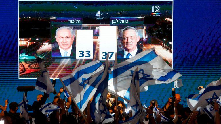 Les partisans de l'alliance bleue et blanche agitent des drapeaux à la sortie des urnes