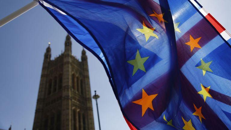 Un activiste agite une combinaison de drapeaux de l'Union et de l'Union européenne près du Parlement, dans le centre de Londres, le 10 avril 2019. - Le négociateur en chef du Brexit, responsable de l'UE, a déclaré mardi que la longueur de tout retard dans le divorce était celle du bloc. peut accorder à la Grande-Bretagne dépendra de ce que le Premier ministre Theresa May apporte à un sommet pressant. (Photo de Tolga AKMEN / AFP) (Le crédit photo devrait correspondre à TOLGA AKMEN / AFP / Getty Images)