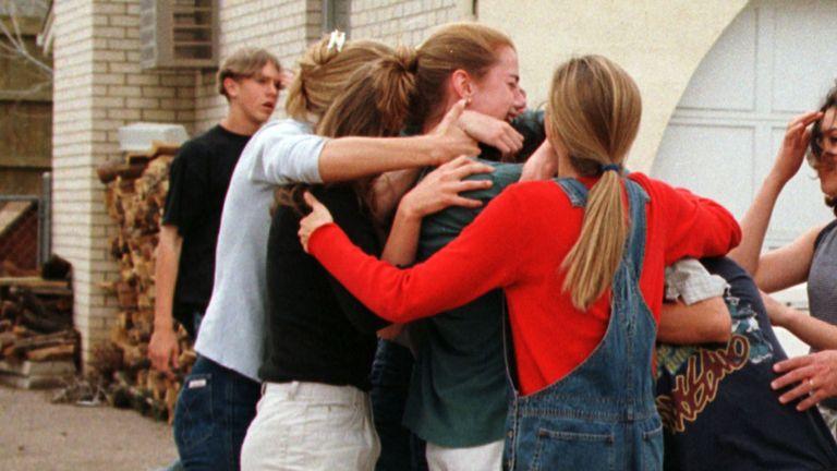 """SHOOTINGRTRO9XJ21 Avril 1999Littleton, USAColombines et amis se précipitent et prennent dans les bras un ami qui vient de s'échapper de l'intérieur du lycée où des hommes armés ont ouvert le feu sur des étudiants terrifiés, tuant peut-être 23 personnes avant de se suicider, a déclaré la police. Jeff Stone, shérif du comté de Jefferson, a déclaré que les hommes armés, étudiants à l'école, avaient été retrouvés morts dans la bibliothèque lors d'une """"mission suicide""""."""