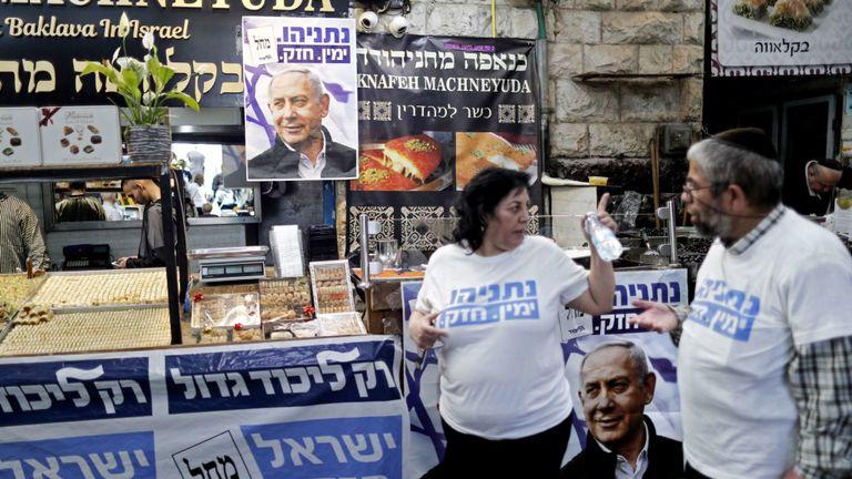 Des partisans du Premier ministre israélien, Benjamin Netanyahu, se tiennent à côté d'affiches portant son portrait au marché Machane Yehuda à Jérusalem le 8 avril 2019, un jour avant les élections. - Les Israéliens votent le 9 avril lors d'une élection décisive sur la prolongation du mandat du Premier ministre Benjamin Netanyahu au pouvoir, malgré des accusations de corruption à son encontre et un défi de taille lancé par un ancien chef militaire. (Photo de THOMAS COEX / AFP) (Le crédit photo doit se lire comme suit: THOMAS COEX / AFP / Getty Images
