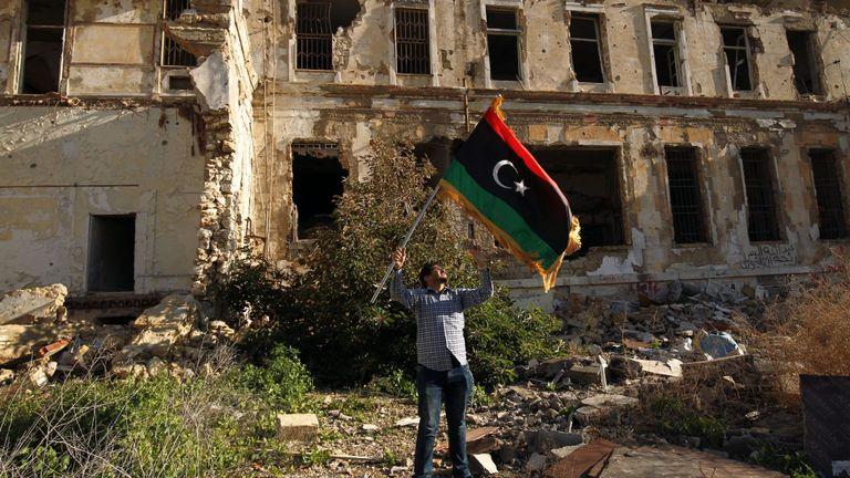 Un homme libyen brandit le drapeau national lors d'un rassemblement pour marquer le huitième anniversaire du soulèvement dans la deuxième ville de Benghazi, en Libye, le 17 février 2019. - Huit ans après la révolte en Libye contre Moammar Kadhafi régime autoritaire, un État moderne et démocratique reste un rêve lointain dans un pays qui glissait de crise en crise