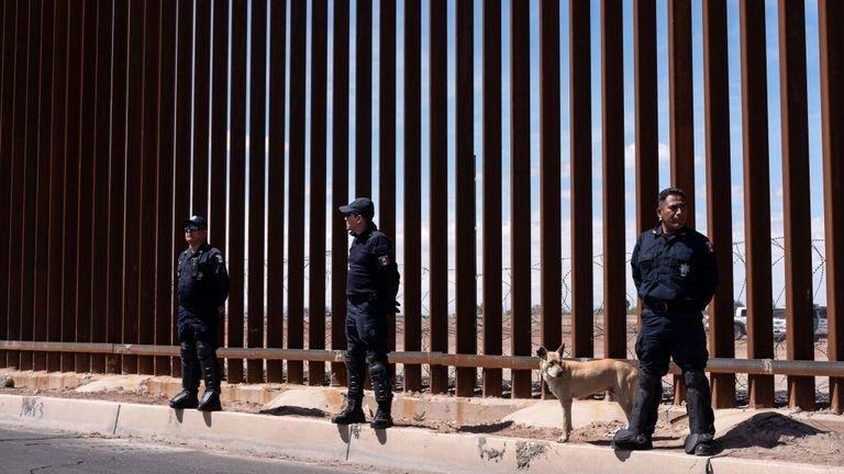 La police des frontières mexicaine se tient devant la clôture en acier et ardoise qui sépare les deux pays