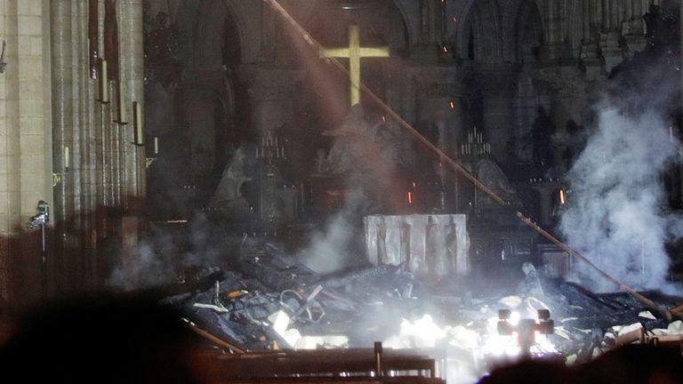 La fumée monte autour de l'autel devant la croix à l'intérieur de Notre Dame