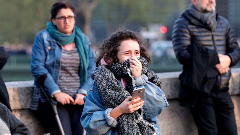 Une femme réagit en regardant les flammes engloutir le toit de la cathédrale Notre-Dame à Paris